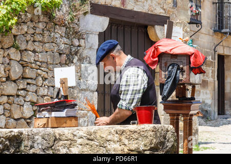 Santillana, Spain - 7th July 2018: Man with old fashioned plate camera. He takes photos of tourists. - Stock Image