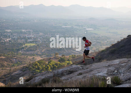An adventurous male trail runner runs down rocky trails as daylght fades while exploring the desertic expanses of the mountains surrounding the town o - Stock Image