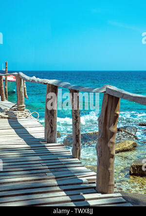 Old, wooden pier on a tropical, asian beach - Stock Image