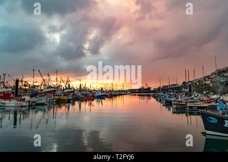 Newlyn, Cornwall, UK. 3rd Apr, 2019. UK Weather. A brief splash of colour at Newlyn Harbour this morning, before the sun dissapeared behind a thick band of clouds. Feeling much colder than yesterday. Credit: Simon Maycock/Alamy Live News - Stock Image