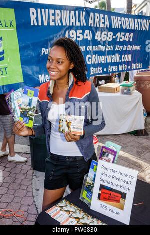 Fort Lauderdale Ft. Florida Las Olas Boulevard Black woman job brochures free information promotion Riverwalk area neighborhood - Stock Image