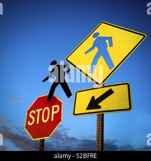 Pedestrian sign hole and pedestrian figure goung to an Stop Sign - Stock Image
