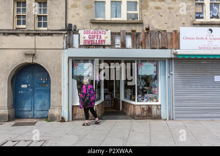 Woman looking the showcase of the old fashion shop of ornaments gifts jewellery at Hastings, East Sussex, England , UK - Stock Image