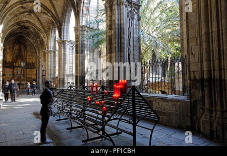 A Woman Stands At A Candle Rack In The Cloister Garden Area Of Barcelona Cathedral Spain - Stock Image