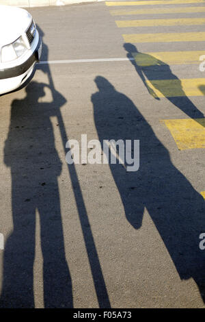 Shadows of pedestrians waiting at a pedestrian crossing. - Stock Image