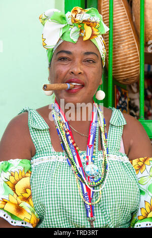 Colourfully dressed cuban lady sitting smoking a large cigar in one of the streets in the Old Town of Havana, Cuba, Caribbean - Stock Image