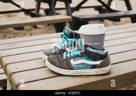 Ironic that a cup with 'leave only footprints' - an anti-litter message, is left discareded in a pair of - Stock Image