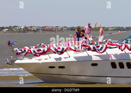 Decorated boat motors past during the Blessing of the Fleet festival at Kemah boardwalk Texas - Stock Image