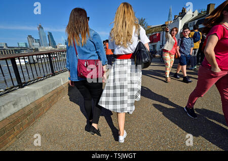 London, England, UK. Two young women  walking on the South Bank, City of London in the background (left) - Stock Image