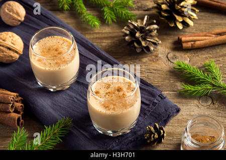 Eggnog with cinnamon in glasses over rustic wooden background with Christmas decor  - homemade Christmas festive - Stock Image