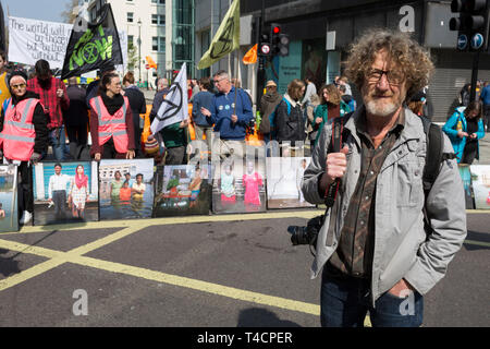 Photographer Gideon Mendel and some of his flood victim portraits 'Drowning World' during the climate Change protest with Extinction Rebellion blocking Oxford Street and simultaneously stop traffic across central London including Marble Arch, Piccadilly Circus, Waterloo Bridge and roads around Parliament Square, on 15th April 2019, in London, England. - Stock Image