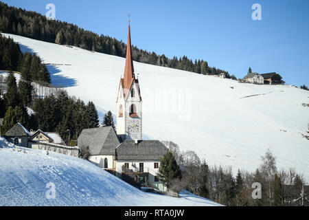 Catholic church in the Italian dolomites in wintertime with snow. San Volfango church in Sorafurcia, South Tyrol, Italy. Tower bell - Stock Image