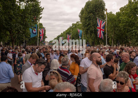 Crowds gather along The Mall towards Buckingham Palace to watch a flypast of Royal Air Force Aircraft to commemorate the RAF's centenary in July 2018 - Stock Image