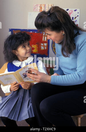 Woman reading with primary school infant - Stock Image