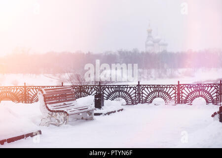 Winter city landscape. Winter park covered with snow. A bench under a snow-covered tree in city park. - Stock Image