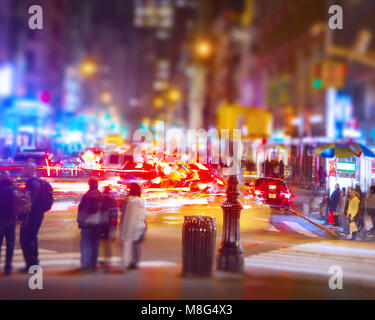 A long exposure of a Manhattan street corner showing the traffic trails and people waiting to cross. - Stock Image