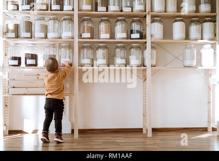 A rear view of small toddler boy standing by shelf with glass jars in zero waste shop. - Stock Image