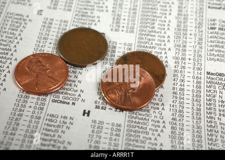 Close-up of pennies on newspaper financial section - Stock Image