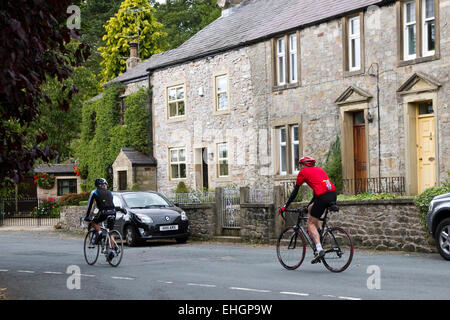 Cyclists riding through village of Newton in the Forest of Bowland (AONB), Ribble Valley district of Lancashire, - Stock Image