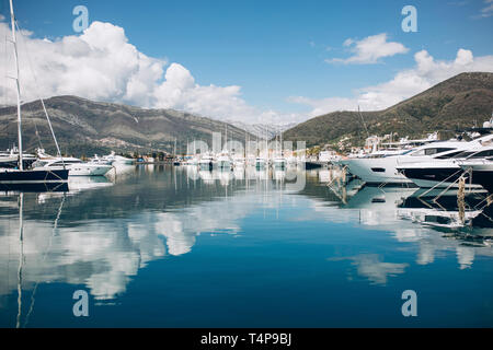 Many yachts moored at the coast in Porto Montenegro in Tivat in Montenegro against the backdrop of a beautiful mountain landscape. Summer sea vacation - Stock Image