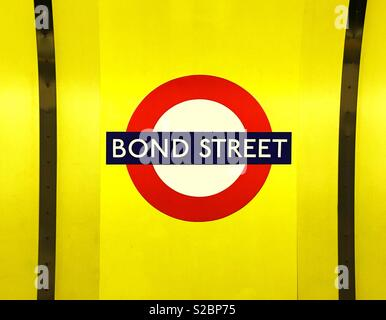 The Iconic sign of London Underground and the station is Bond Street - an area famous for its luxury shopping brands. A colourful and graphic image with no people. Photo Credit - © COLIN HOSKINS. - Stock Image