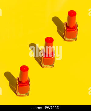 Bottles with red crimson nail polish arranged in diagonal on solid yellow background. Bright sunlight strong shadows. Creative minimalist funky style  - Stock Image