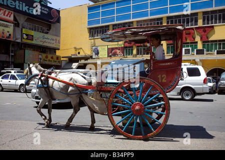 A kalesa makes its way down a street in Manila, Philippines. - Stock Image