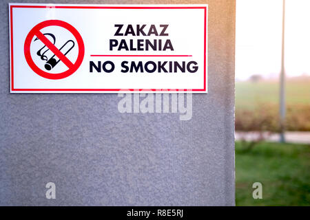bilingual no smoking text and sign in Polish and English on the wall, blurred background, warm sun right top - Stock Image