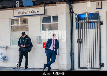 Two passengers looking at their mobile phones on the platform at Elephant & Castle station in south London, while waiting for a train. - Stock Image