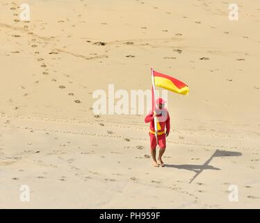 RNLI lifeguard on duty carrying a red and yellow flag across the beach,Riviere Towans beach, Phillack, Hayle,cornwall,England,UK - Stock Image