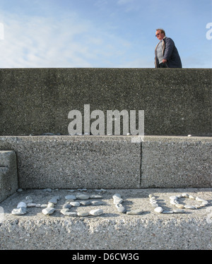 The word 'Hello' made out of beach pebbles arranged in the sun on a step by a beach. A man is walking past - Stock Image