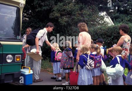 primary school children getting on bus to go on school trip - Stock Image