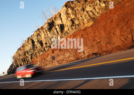 A road cut along highway 61 in northern Minnesota showing a basaltic lava flow on top of an underlying sedimentary - Stock Image