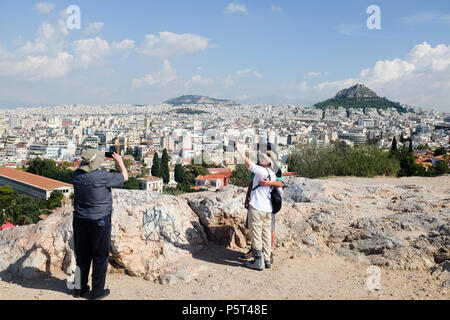 Tourists taking Photos/Selfies from the Acropolis, enjoying the views of Athens and Mount Lycabettus ( Lycabettos ), Athens, Greece. - Stock Image