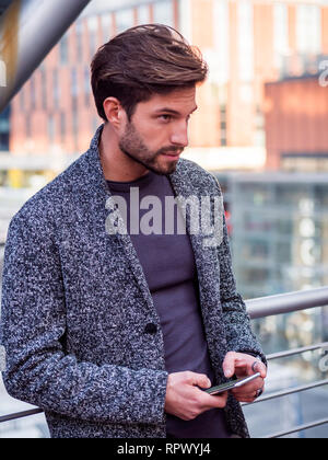 Handsome trendy man typing on cell phone - Stock Image