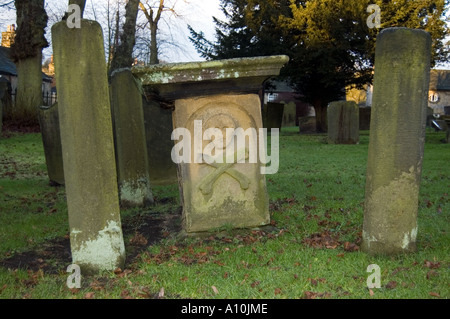 Skull & crossbones grave in Eyam is the famous plague village which went into voluntary quarantine when the - Stock Image
