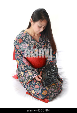 Japanese Lady Sitting on the Floor Wearing a Traditional Blue and Red Patterned Kimono and Holding a Fan - Stock Image