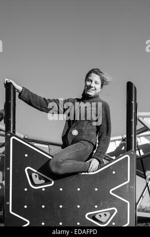 Girl smiling down from the top of a climbing wall in a playground in Daventry, Northamptonshire during the winter - Stock Image