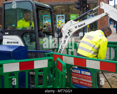 Workmen operating a small Bobcat excavator digging a trench in the pavement for installation of an electrical power cable - Stock Image