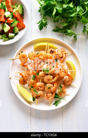 Grilled shrimp skewers. Prawns skewers with greens, spices and lemon on white plate over wooden table. Tasty seafood. Healthy snack. Top view, flat la - Stock Image