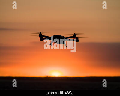 Drone at Sunset: A small drone hovers over the Ottawa River just as the sun sets. - Stock Image
