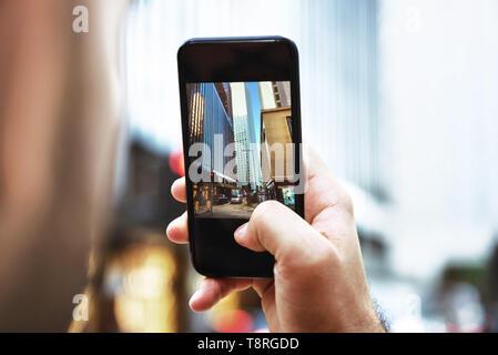 Man takes mobile photo of big city - Stock Image