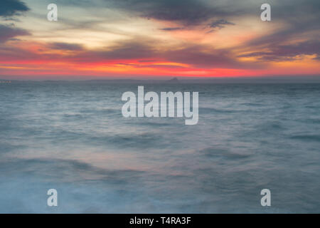 Newlyn, Cornwall, UK. 18th Apr, 2019. UK Weather. It was windy and mild in Cornwall this morning, with a vivid red colour at sunrise over the sea at Mounts Bay. Credit: Simon Maycock/Alamy Live News - Stock Image