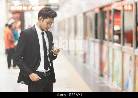 Young hipster asian businessman using smartphone while waiting for a train in subway. Concept of wireless technology, mobile internet and online busin - Stock Image