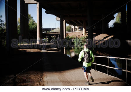 A jogger running alongside the Tame Valley Canal, underneath the Gravelly Hill Interchange (aka Spaghetti Junction), Birmingham, West Midlands, UK. - Stock Image