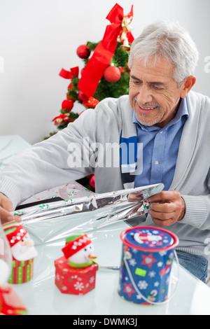 Man Wrapping Christmas Present - Stock Image