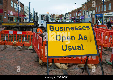 Business as usual sign in a pedestrianised High Street blocked by major road works - Stock Image