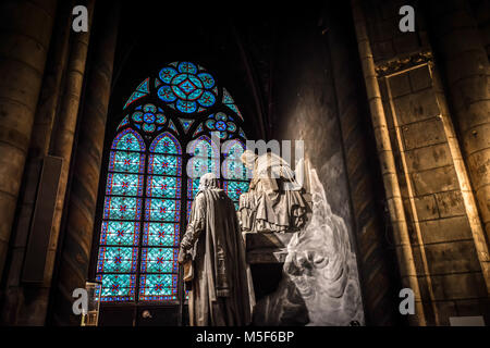 Gorgeous blue and green stained glass window with large statues in the interior of the Notre Dame Cathedral in Paris - Stock Image