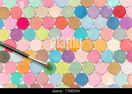 Cosmetic brushe laying on large colored eye shadows bundle top view - Stock Image