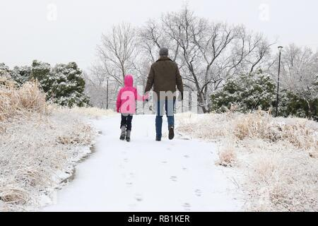Father and daughter walking up a snowy hill holding hands - Stock Image
